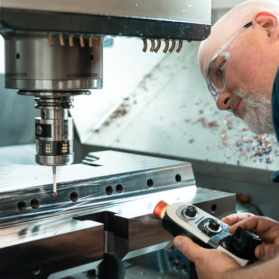 Un employé inspecte une pièce de moule de précision dans un centre d'usinage 5 axes